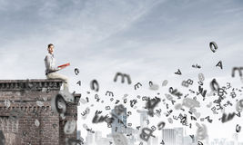 Man on roof edge reading book and symbols flying around Stock Images