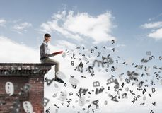 Man on roof edge reading book and symbols flying around. Young man in casual sitting on building edge with red book in hands Royalty Free Stock Image