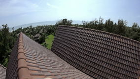 Man on the roof of a house. Near the sea stock footage