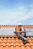 Man on roof installing solar panels Stock Photography