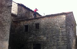 Man on the roof. Man on the old stone hous roof working Stock Images