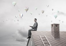 Man on roof reading book and aerostats flying in air Royalty Free Stock Photo