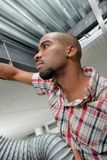 Man in roofspace with ventilation hose stock photo