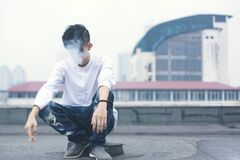 Man on rooftop smoking Stock Photography