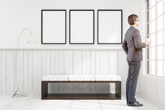 Man in a room with a bench and posters Stock Photography