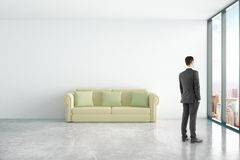 Man in room with couch. Thoughtful businessman in concrete interior with comfortable green couch and window with city view. 3D Rendering Stock Photography