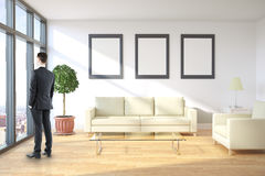Man in room with frames. Thoughtful businessman looking out of window in living room interior with city view, furniture and blank picture frames on wall. Mock up Royalty Free Stock Photo