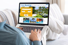 Man in room holding laptop with online search booking hotel Royalty Free Stock Photos