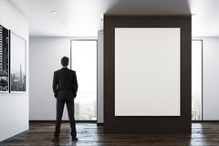 Man in room with poster. Back view of young businessman standing in modern room interior with empty poster on wall and city view. Mock up, 3D Rendering Royalty Free Stock Photos