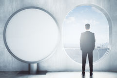 Man in room with round banner. Back view of thoughtful man looking out of window in concrete interior with round banner. Mock up, 3D Rendering Stock Photography