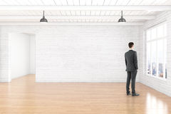 Man in room. Thoughtful businessman in empty room interior with blank white brick wall, wooden floor, ceiling and window with city view. Mock up, 3D Rendering Stock Photo