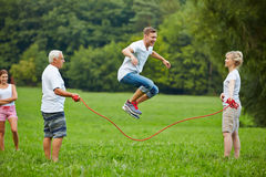 Man rope skipping with jumping rope. With his family in nature Stock Images