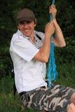 Man on rope swing. Smiling man having fun on a rope swing Stock Images