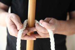 Man with rope and wood pole Stock Image