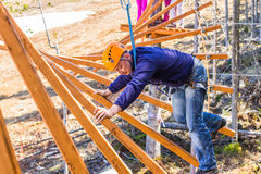 A man in a ropes course. The man climbs into ropes course Stock Photos