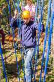 A man in a ropes course. The men climbs into ropes course Royalty Free Stock Image
