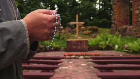 Man with rosary near cross at outdoor. In summer day stock video footage