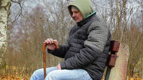 Man with rosary and walking stick on bench stock footage