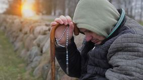 Man with rosary and walking stick near stone fences stock footage