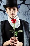 Man with a rose. Portrait of a young gentlemen wearing dinner jacket and black top hat. Shot in a studio Royalty Free Stock Images