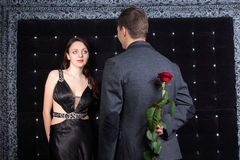Man with Rose Behind his Back Talking to his Girl Stock Photo