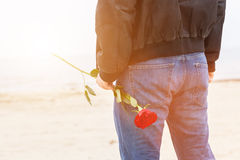 Man with a rose behind his back waiting for love. Romantic date on the beach Stock Photo