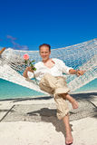 Man with a rose in hands in a hammock, Stock Photos