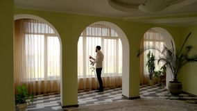 Man with rose indoor. Guy looking out the window stock footage