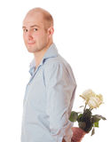 Man with roses. Picture of a young male hiding a flower behind his back, isolated on white Royalty Free Stock Image
