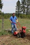 Man rototilling garden. Royalty Free Stock Image