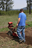Man rototilling garden. Man rototilling the ground, getting it ready for a garden Royalty Free Stock Images