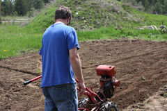 Man rototilling garden. Man rototilling the ground, getting it ready for a garden Stock Photography