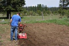 Man rototilling garden. Man rototilling the ground, getting it ready for a garden Stock Photos