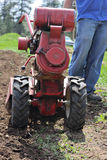 Man rototilling garden. Man rototilling the ground, getting it ready for a garden.  Close-up of rototiller Stock Photo