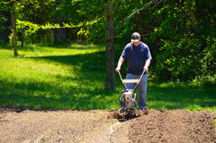 Man rototilling the garden Stock Photo