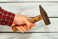Male hand in checkered shirt holding hammer Royalty Free Stock Images