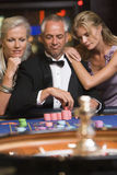 Man at roulette table with beautiful women. Man at roulette table surrounded by beautiful women royalty free stock photography