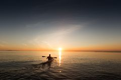 A man in a rowboat going towards the sunrise royalty free stock image