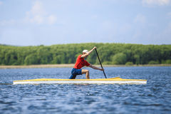 Man rower in a canoe rowing Stock Images