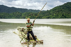 A man rowing the bamboo raft on the lake. LAMDONG,VIETNAM- JULY 21: the man rowing bamboo raft on the lake in Lamdong, Vietnam on July 21, 2015 Royalty Free Stock Photo