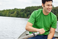 Man rowing a boat Stock Images