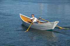 Man rowing a boat in harbor Royalty Free Stock Image