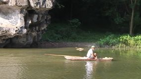 The man rowing a boat by his legs. NINH BINH, VIETNAM - AUGUST 1: The man rowing a boat by his legs on Tam Coc river on August 1, 2012 in Ninh Binh, Vietnam stock footage