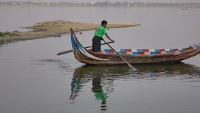A man rowing boat on lake in Mandalay, Myanmar stock footage
