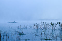 A man rowing his boat in thick fog Stock Image