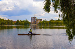 Man is rowing on a kayak boat on Ivano-Frankivsk city lake in sp Royalty Free Stock Photography