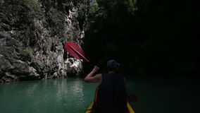 Man rowing kayak and floats along the gorge. Elderly man rowing a kayak and floats along the gorge across the azure sea water stock video