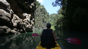 Man rowing kayak and floats along the gorge stock video footage