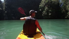 Man rowing kayak on green sea water stock footage