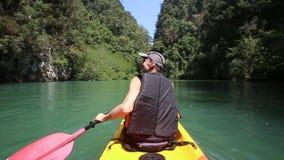 Man rowing kayak and looking around stock video footage